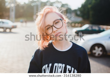 Fashion details.Close up trendy image os sexy fit hipster woman wearing retro denim jeans and warm sweater,swag style,print t-shirt. posing at he street at sunny day.pink hair  - stock photo