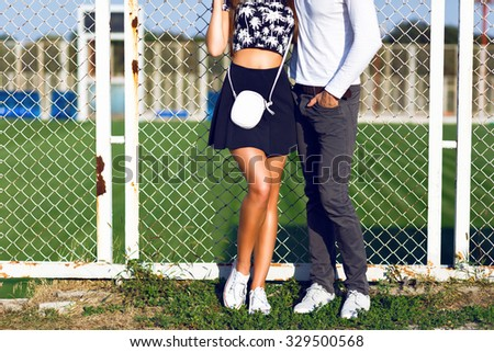 Fashion details, young hipster couple posing at sports ground, wearing trendy hipster black and white casual clothes and sneakers, sunny day , bright colors. - stock photo