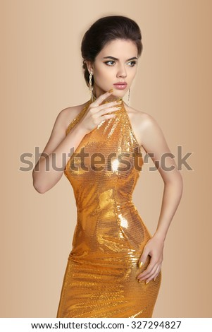 Fashion Elegant brunette woman in golden dress isolated on beige background. Makeup. Jewelry. Gown.