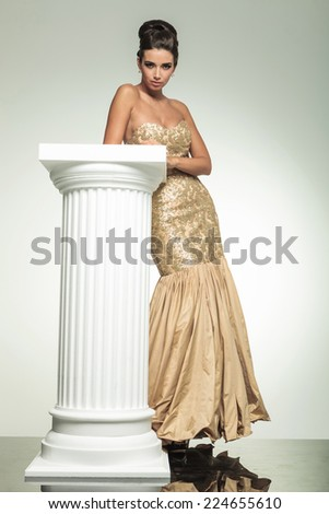 fashion elegant woman in golden dress leaning on a column in studio, full body picture - stock photo