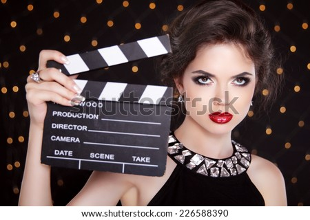 Fashion elegant woman with sexy red lips holding cinema clap. Super star model shot - stock photo