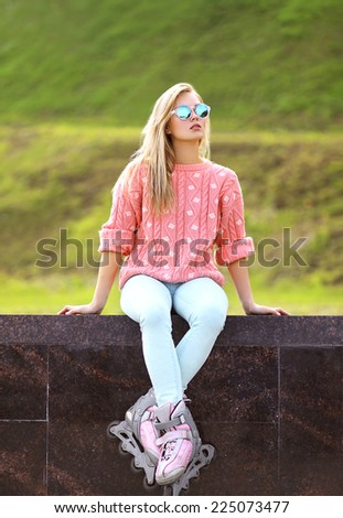 Fashion, extreme, youth and people concept - pretty stylish blonde girl in sunglasses with roller skates in the city park, cool roller girl posing outdoors