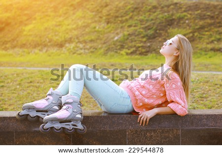 Fashion, extreme, youth and people concept - pretty stylish blonde with roller skates in the city park, cool roller girl posing outdoors - stock photo