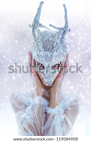 Fashion fantastic miracle model face in silver mask Christmas deer horns on white snow background - stock photo