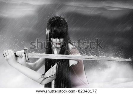 Fashion fantasy portrait of young pretty brunette woman fighter with sword in mist - stock photo