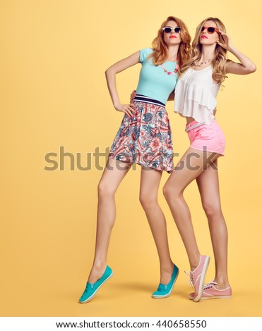 Fashion. Fashion hipster woman, fashion summer outfit having fun. Fashion sisters friends crazy cheeky emotions.Girl in fashion sunglasses, fashion wavy hairstyle posing on yellow.Unusual creative fun - stock photo
