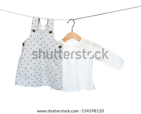 Fashion female child's (baby) dress and shirt hanging on rope isolated on white background/ Baby wear set/ Close-up.