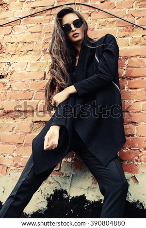 Fashion female model alluring outdoor by the brick wall. City style. Fashion photo.  - stock photo