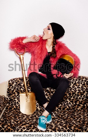 Fashion female model wearing black dress and beanie and pink fur coat licking candy. Freak young Woman sitting on leopard sofa and holding gold helmet and shovel. Vogue style indoors shot  - stock photo