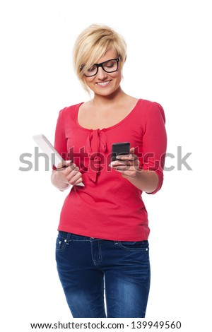 Fashion female using mobile phone and holding digital tablet - stock photo