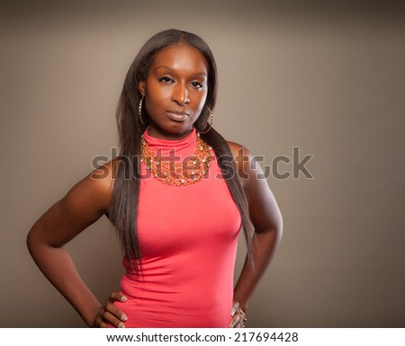 Fashion forward African American woman with part American Indian heritage in a pink dress with jewelry - stock photo