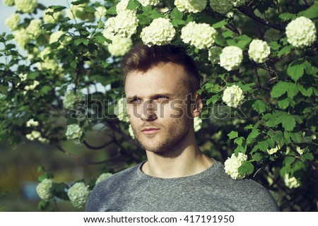 Fashion fresh air concept. Portrait of serious charismatic strong man wearing stylish grey jumper over bush with flowers. Outdoor shot. Attractive look and bottomless eyes - stock photo