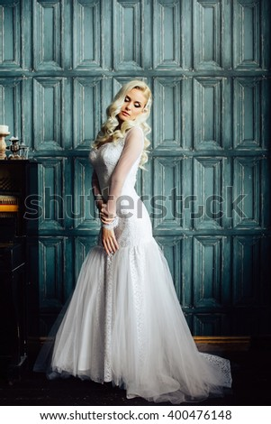 Fashion full length portrait of gorgeous young bride with blonde hair in morning of wedding day. Jewelry. Stylish hair accessories. Blonde woman posing near the piano, looking away - stock photo