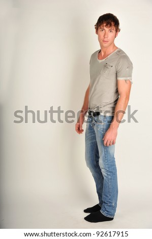 Fashion full-length portrait of the young beautiful man in white t-shirt posing over gray background, series photo