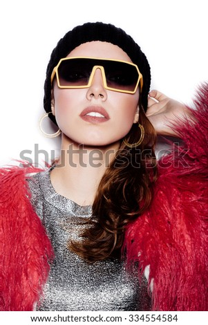 Fashion girl hipster in sunglasses wearing silver dress, pink fur coat, black beanie hat.  White background, not isolated - stock photo