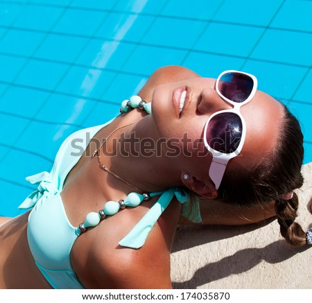 Fashion girl in beautiful bikini lying near swimming pool. Vacations And Tourism Concept. Tropical Resort. - stock photo