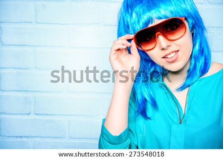 Fashion girl in bright blue wig and sunglasses posing by the urban white brick wall. Beauty, fashion. - stock photo