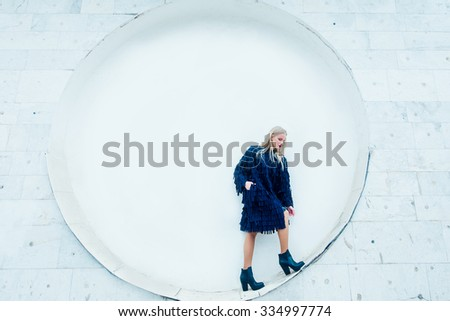 Fashion girl in he blue coat in the circle. Geometry - stock photo