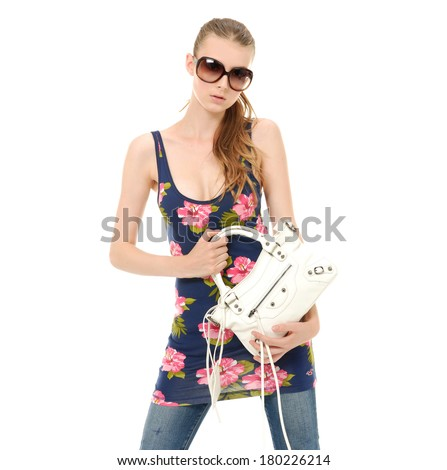fashion girl in sunglasses and in jeans holding bag show in studio,