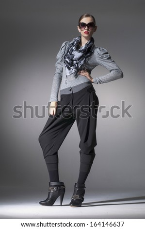 fashion girl in sunglasses with scarf posing in studio