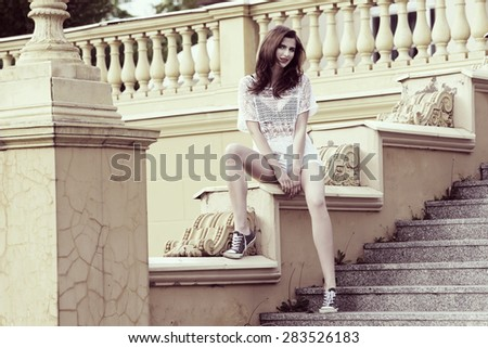 fashion girl in white casual dress , with shortand basket shoes , sitting on old style stairs , looking in camera