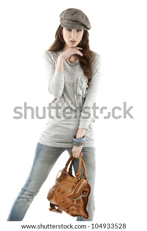 Fashion girl ind jeans with bag show in studio - stock photo