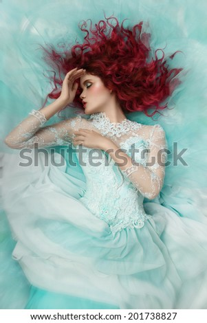 fashion girl lying in a turquoise dress