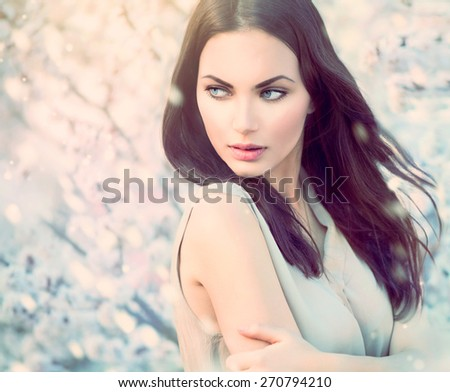 Fashion girl outdoor portrait in blooming trees. Beauty spring Romantic woman in flowers. Sensual Lady. Beautiful Woman Enjoying Nature. Romantic beauty in fantasy orchard - stock photo