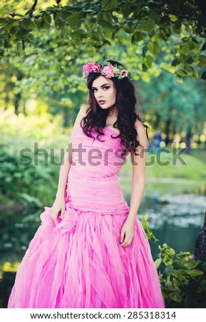 Fashion Girl Outdoors Portrait in Greenery Blooming Trees. Beauty Romantic Woman with Flowers. Beautiful Woman Enjoying Nature - stock photo