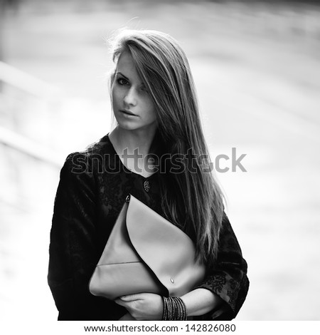 fashion girl outside, black and white portrait of a caucasian young woman