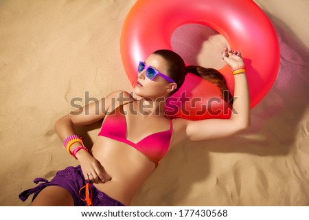 Fashion Girl Portrait. Beautiful Young Woman Sunbathing. Color explosion. Fashionable complements for the beach. Relax on the beach - stock photo