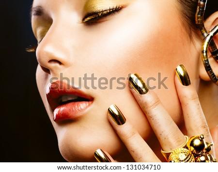Fashion Girl Portrait. Gold Makeup. Golden nails and Eyeshadows. Golden Make-up and Nailpolish - stock photo