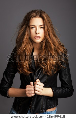 Fashion girl, portrait of young woman posing at studio - stock photo