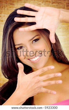 fashion girl smiling and doing a handframe on her face with a golden background
