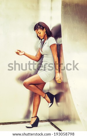 Fashion Girl. Wearing in a gray business dress, drop earrings, a wedge pump, a young black business woman is leaning back against the metal mirror wall, looking down, relaxing, thinking.  - stock photo
