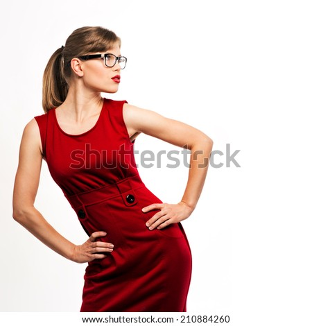 Fashion girl wearing stylish red dress and spectacles. Young gorgeous woman model in optical glasses posing in studio.  - stock photo