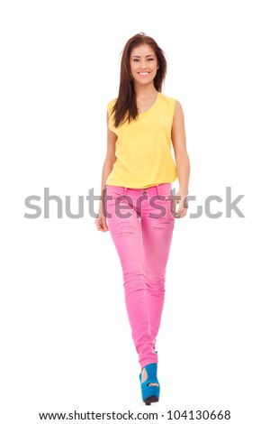 Fashion girl wearing yellow blouse and pink jeans walking towards the camera on white background - stock photo