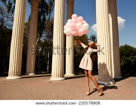 Fashion girl with air balloons walking in park over columns, toned. - stock photo