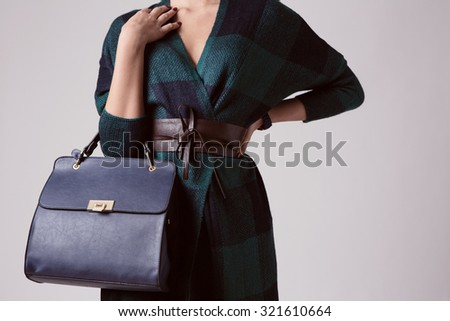 Fashion girl with bag, isolated on gray - stock photo