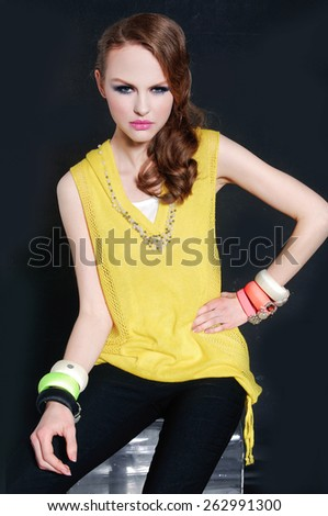 fashion girl with bright make-up-and color bracelet sitting cube on black  - stock photo