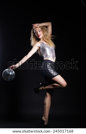 Fashion girl with disco ball over black background - stock photo