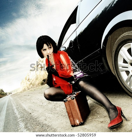 Fashion girl with suitcase stops the car on road