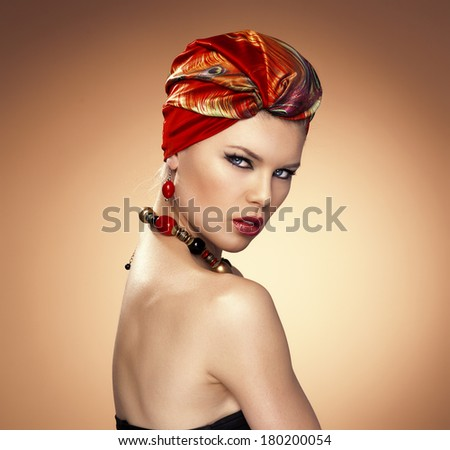 Fashion girl wrapped in red silk turban posing in studio. Young attractive stylish female model wearing expensive jewelery.  - stock photo