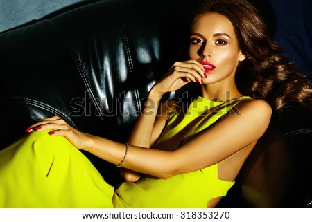fashion glamor stylish beautiful  young woman model with red lips in summer bright colorful   yellow dress sitting on black sofa - stock photo