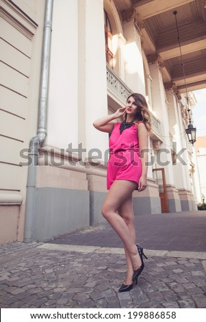 Fashion, glamorous and attractive woman dressed in a sexy sleeveless pink jumpsuit posing in full body length with long legs. Elegant and stylish - stock photo