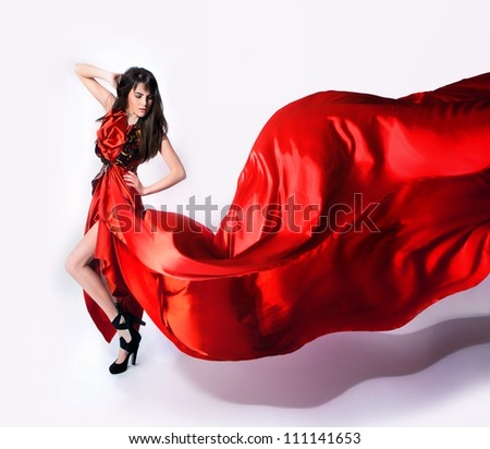 fashion glamour girl with long hairs posing in red long dress