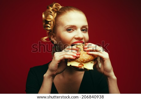 Fashion & Gluttony Concept. Portrait of luxurious red-haired model in black cocktail dress eating burger over red background. Perfect hair, skin, make-up and manicure. Golden accessories. Studio shot - stock photo