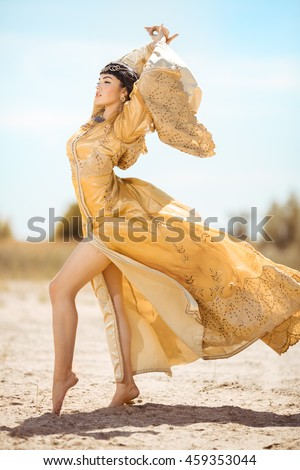 Fashion gorgeous beauty woman with black short haircut and professional make-up of Cleopatra. Girl standing in full lenght in golden dress outdoors in desert. Hot sunny windy weather - stock photo