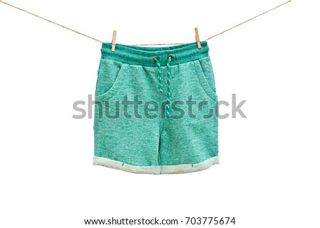 Fashion green baby-boy shorts hanging on rope isolated on white background/ Baby clothes/ Close-up.