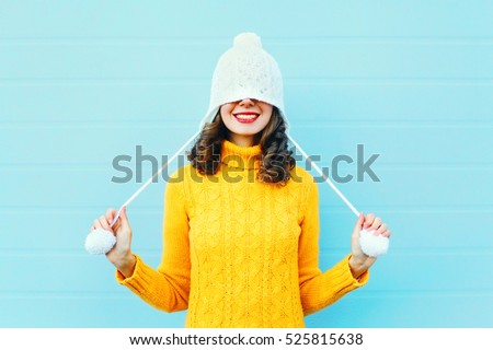 Fashion happy young woman in knitted hat and sweater having fun over colorful blue background
